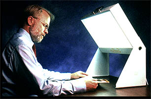 Image of man seated, reading a magazine while facing toward a light box for bright light therapy
